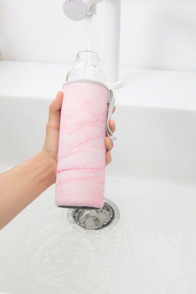 Skleněná láhev s růžovým obalem